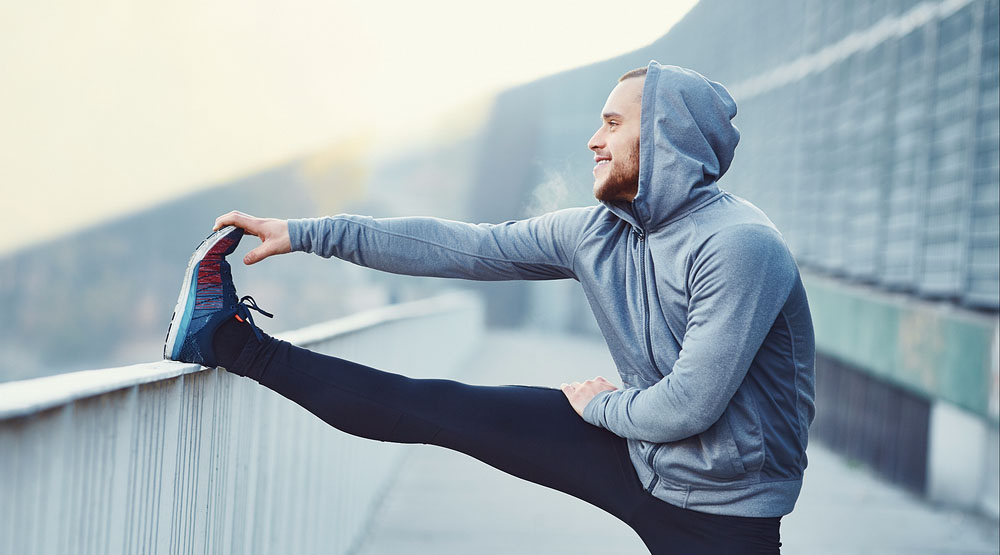 Male runner doing stretching exercise, preparing for morning workout in the park (baranq/Shutterstock)