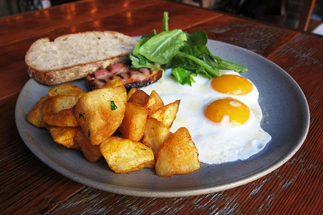Two fried eggs, bacon, and toast (Jess Fleming / Daily Hive)