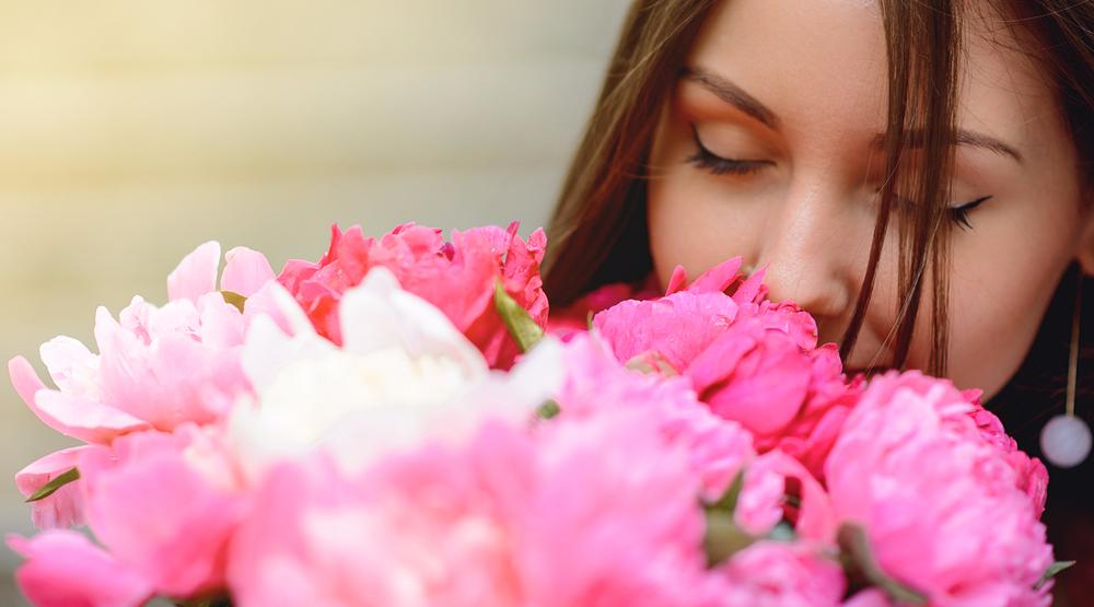 Woman smelling peonies (Patramansky Oleg/Shutterstock)