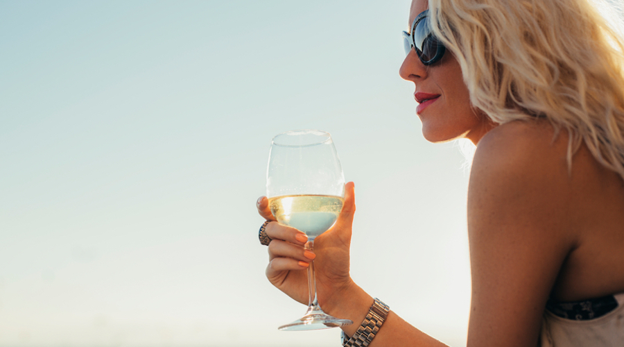 woman at beach drinking wine