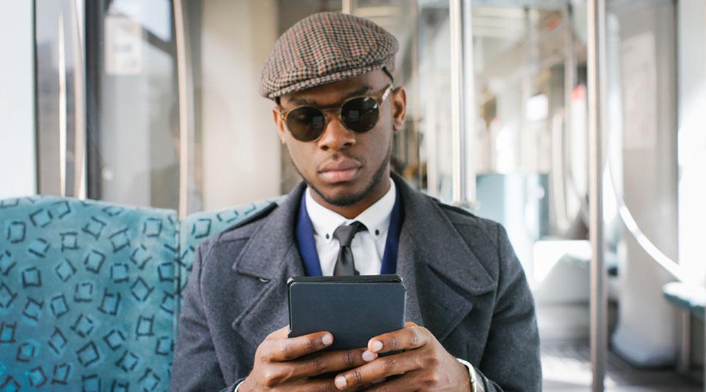 Man reading ebook on kindle on transit stocksy