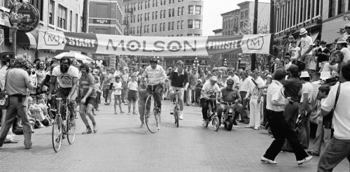 "The first Gastown Grand Prix races featured a number of support events including media races, bed races and pennyfarthing races. The 1975 Gastown Grand Prix, shown here, also featured a celebrity race with Provincial MLA and former BC Lion Emery Barnes (left) getting off to a quick start ahead of Mayor Art Phillips (white collar) and other riders. (Photo by Lorne ""Ace"" Atkinson)"