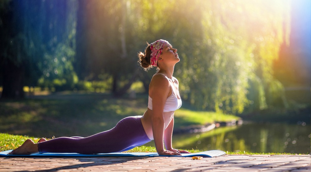 Woman doing yoga outdoors (lkoimages/Shutterstock)