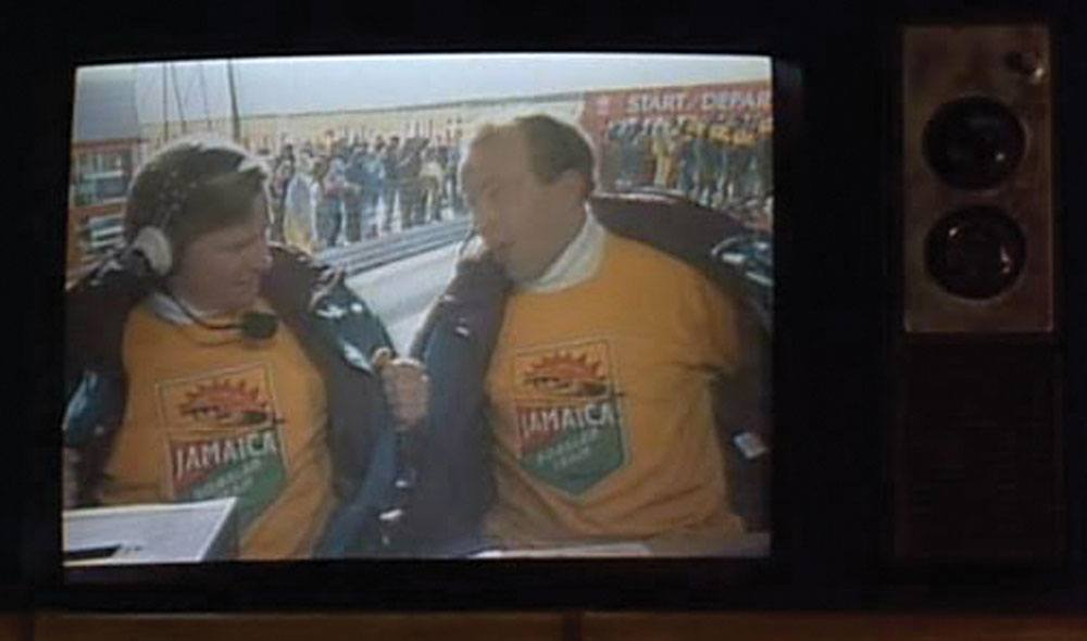 Broadcaster John Morgan (left) wearing the yellow Jamaican bobsled team sweater in his cameo appearance in the 1993 film Cool Runnings (RR Auction)
