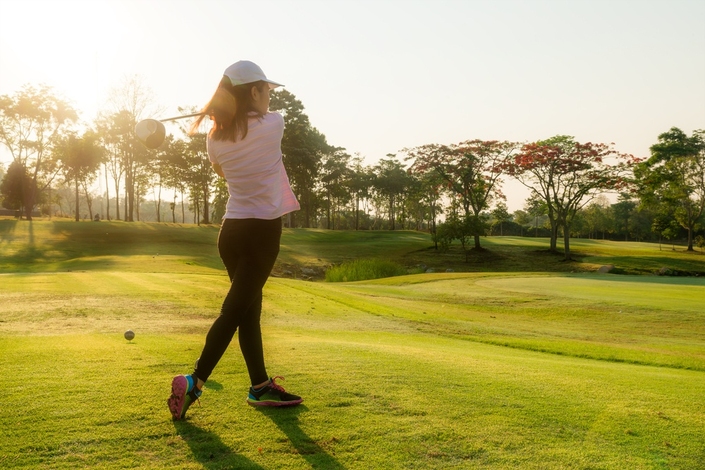 A woman takes a swing on a golf course (Shutterstock)