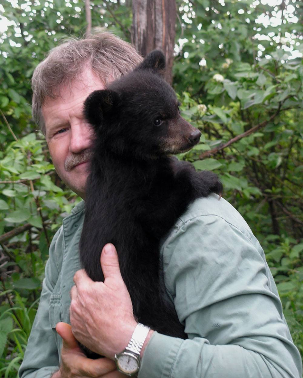 Northern Lights Wildlife Shelter co-founder Peter Langen cares for an orphan black bear at his facility in Smithers, BC (Northern Lights Wildlife Shelter).jpg