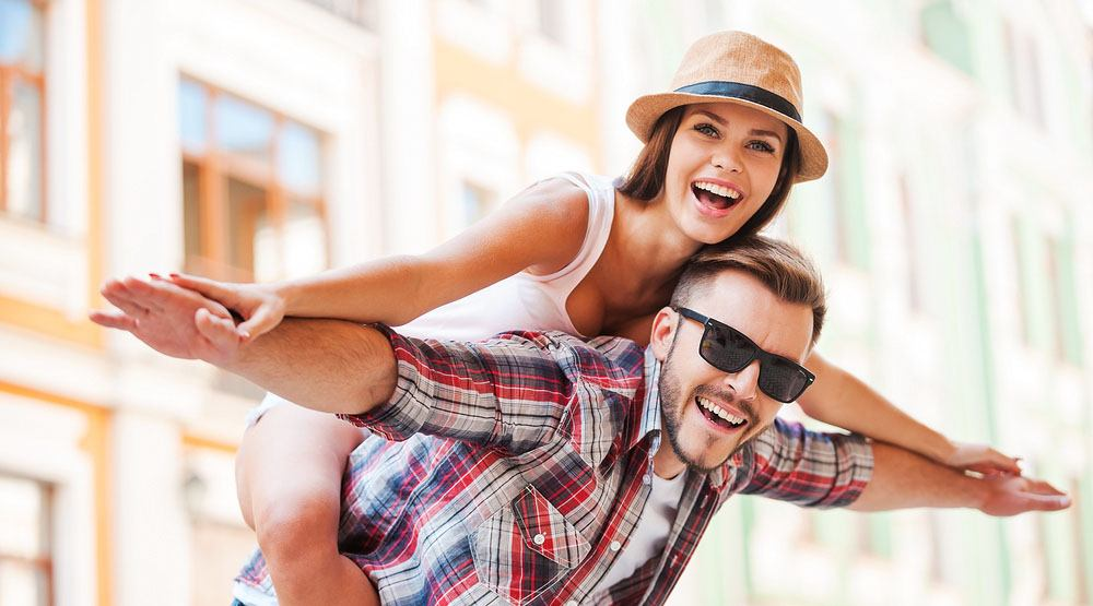 Happy young man piggybacking his girlfriend while keeping arms outstretched g stockstudio shutterstock.jpg