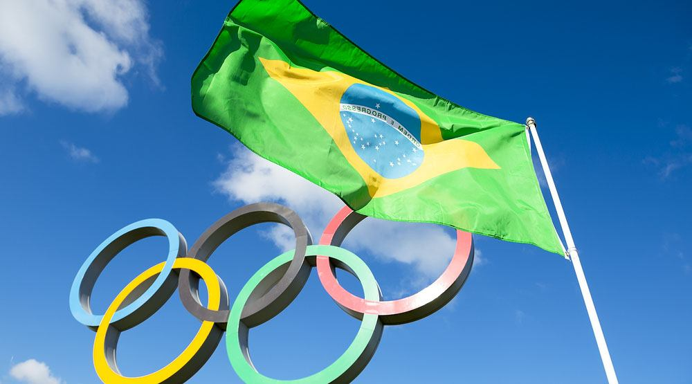 Brazilian flag flies next to the olympic rings lazyllama shutterstock