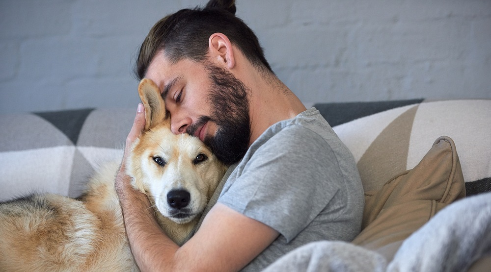 Hipster man snuggling and hugging his dog showing close friendship and a loving bond between owner and pet husky daxiao productionsshutterstock