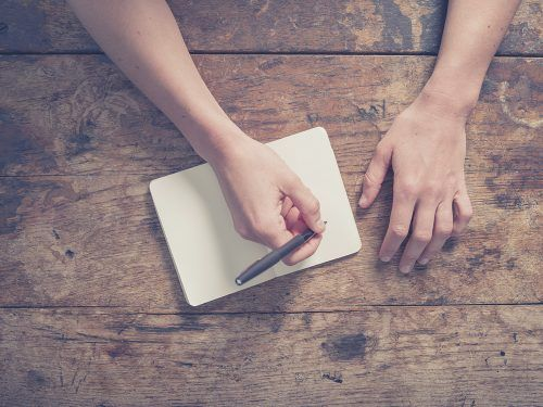 Image: iStock/Close up on the hands of a young woman as she is writing in a small notepad at a wooden table