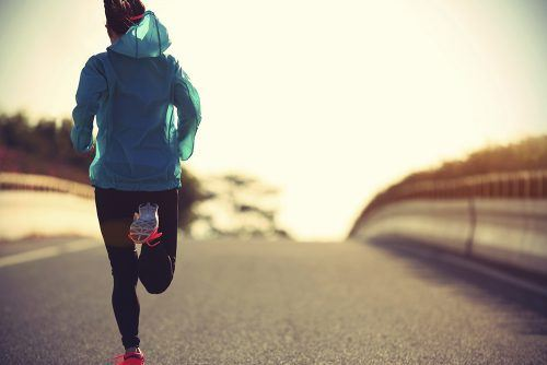 Image: iStock/young fitness woman runner running on sunrise road