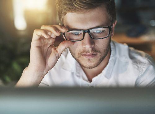 Image: iStock/Shot of a young designer adjusting his glasses as he looks at his computer screen