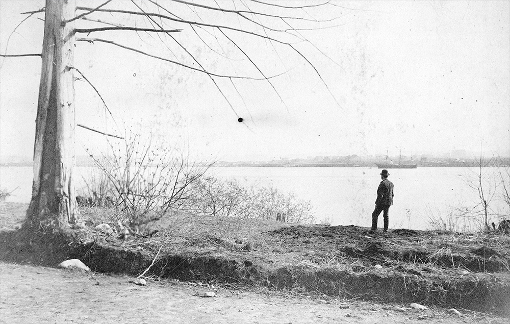 1888: A man takes a break from building the road through Stanley Park to look back at the city (Vancouver Archives)