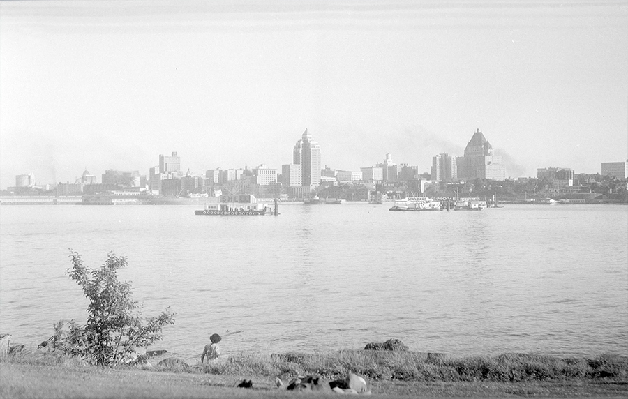 1950: Another shot of the skyline with a couple people relaxing on the grass and on the beach in the foreground. (Vancouver Archives)