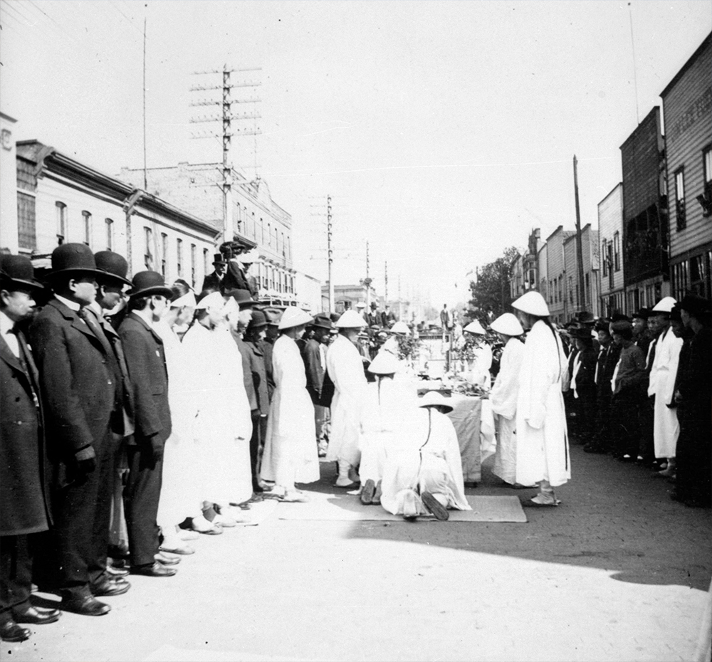 1889: Men don traditional dress for a funeral procession in the middle of Chinatown. (Vancouver Archives)