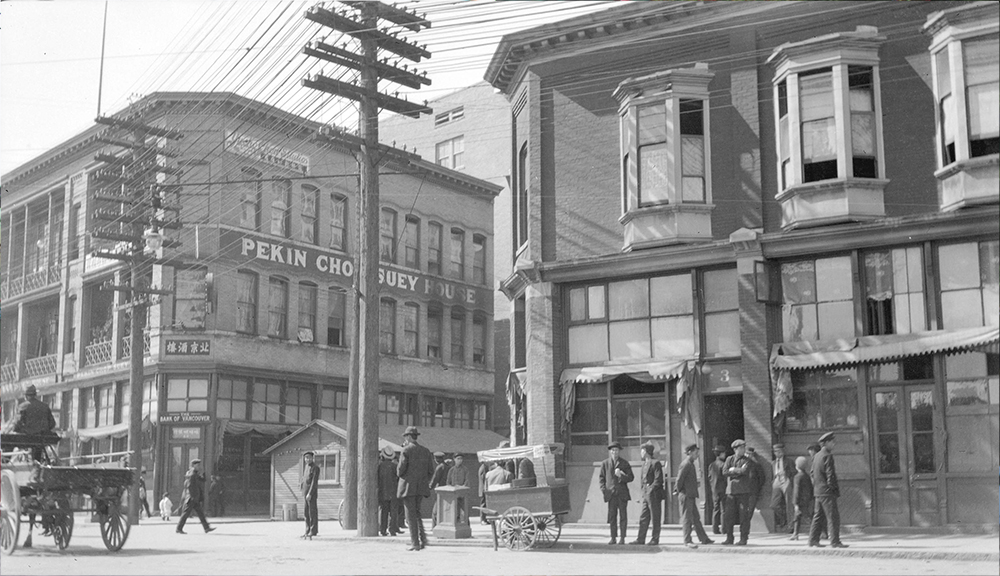 1910: People congregate on the street near the Chinese Freemasons Building at left. (Vancouver Archives)