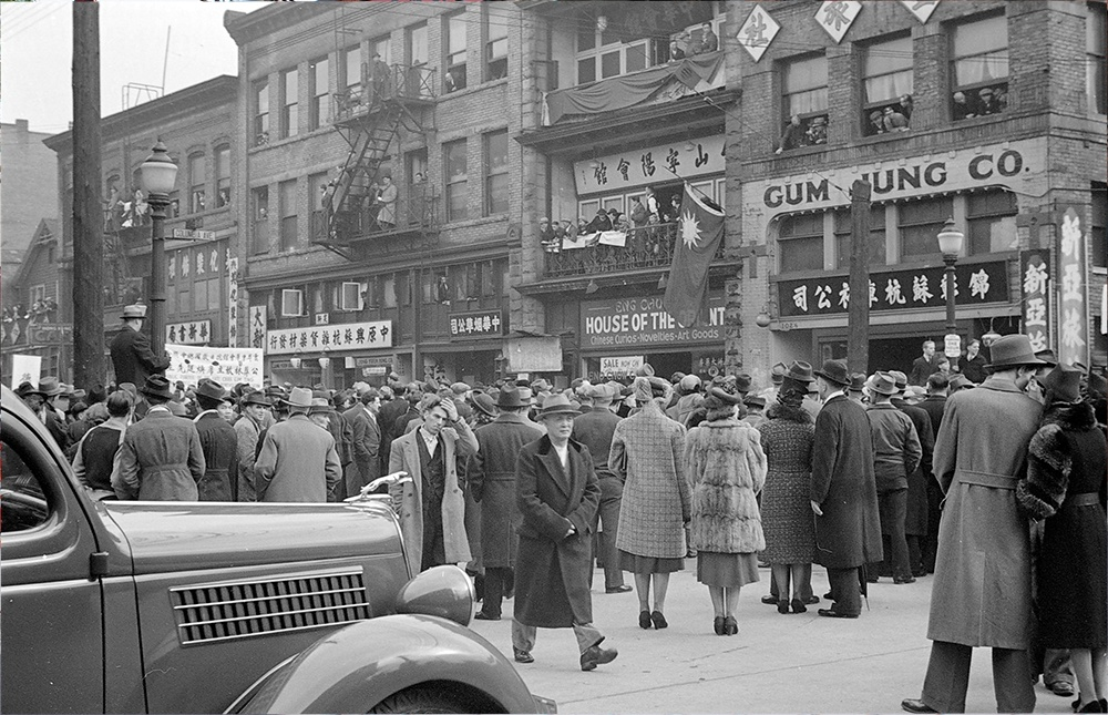 1939: A crowd of both Chinese and European-Canadians has gathered to watch a funeral procession. (Vancouver Archives)