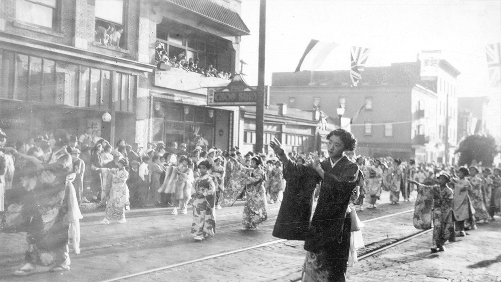 1937: Crowds watch Japanese women and girls in traditional clothes taking part in a parade down Powell Street. (Vancouver Archives)