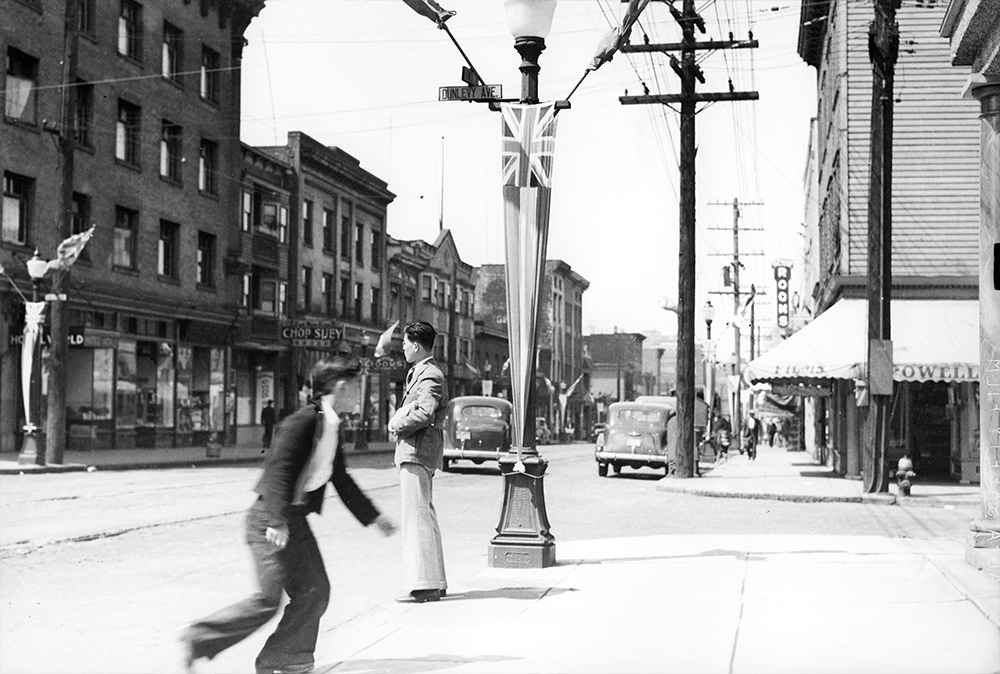 1939: Two Nikkei cross Powell Street by a lightpost emblazoned with the Union Jack. (Vancouver Archives)
