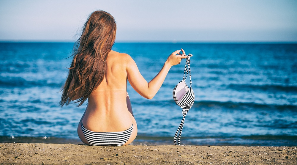 Woman topless on a beach leszek glasnershutterstock