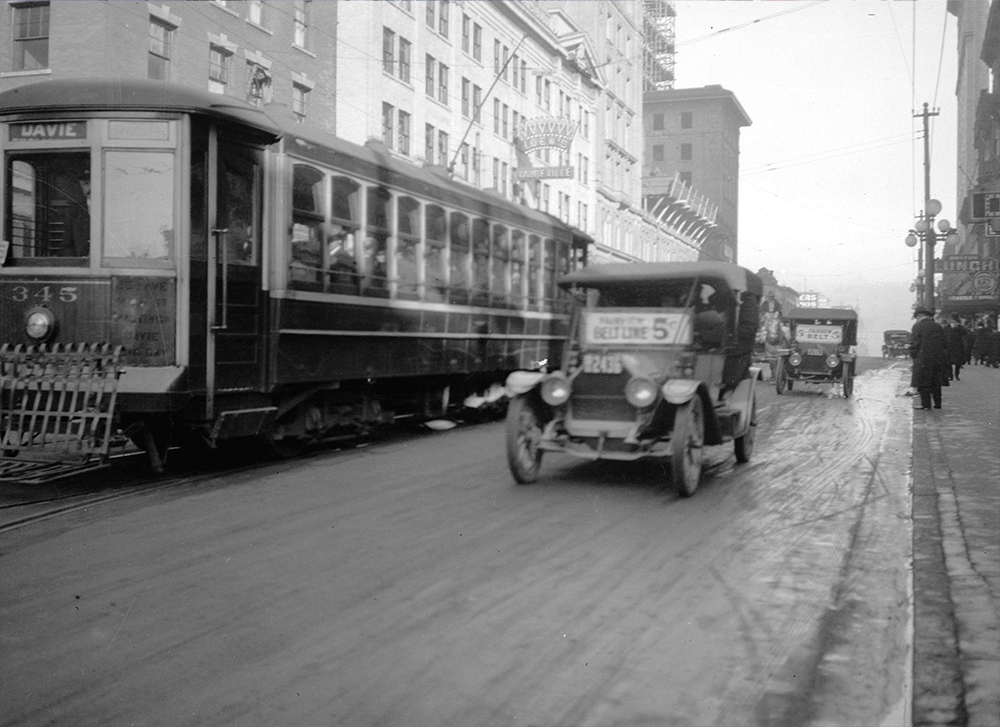 1910s: Taxis and streetcars driving down Granville Street. (Vancouver Archives)