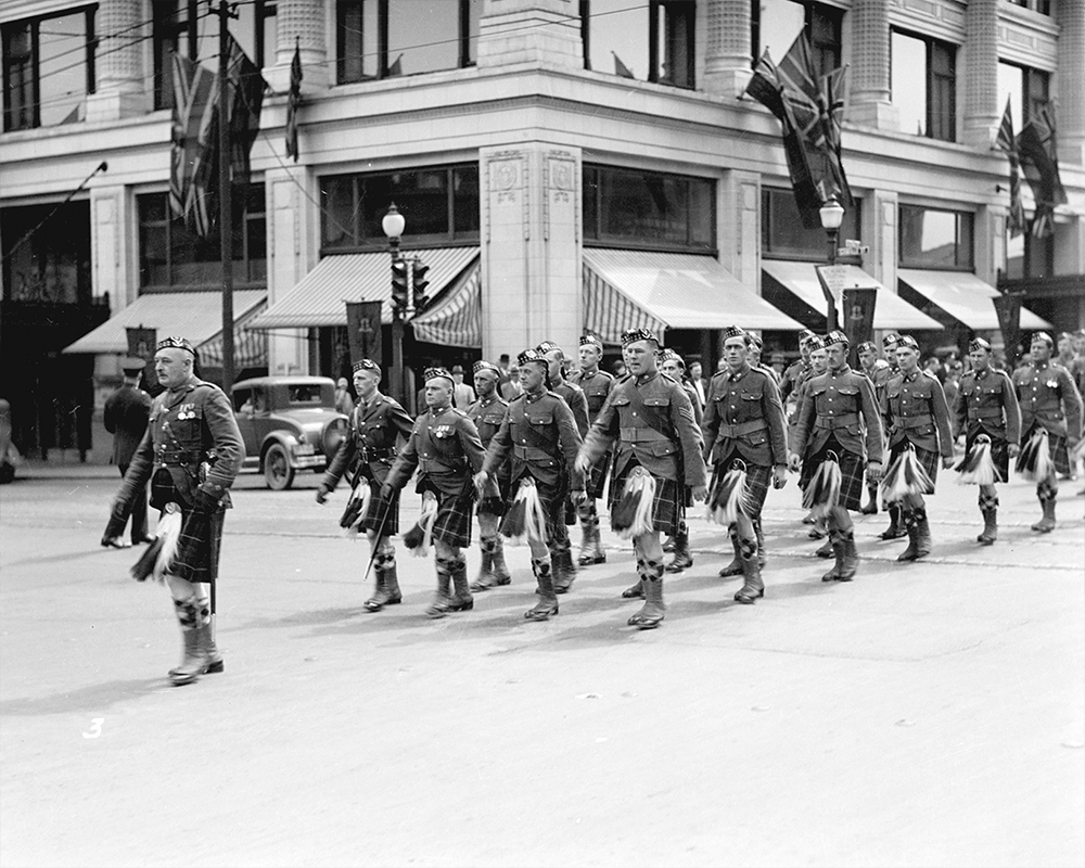 1930: Soldiers from the Seaforth Highlanders march in front of the recently expanded Hudson's Bay Company store. (Vancouver Archives)