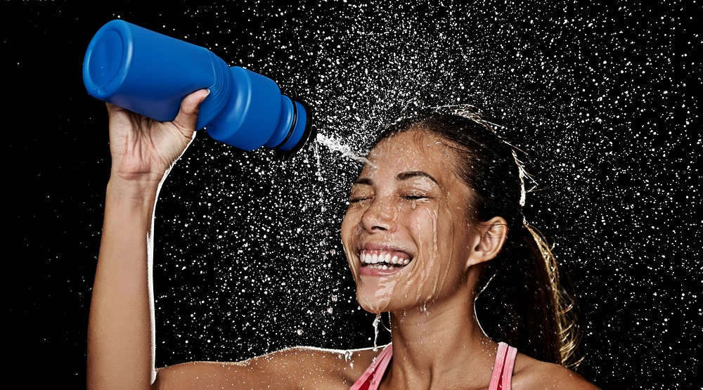 Woman drinking water from a sports water bottle maridavshutterstock