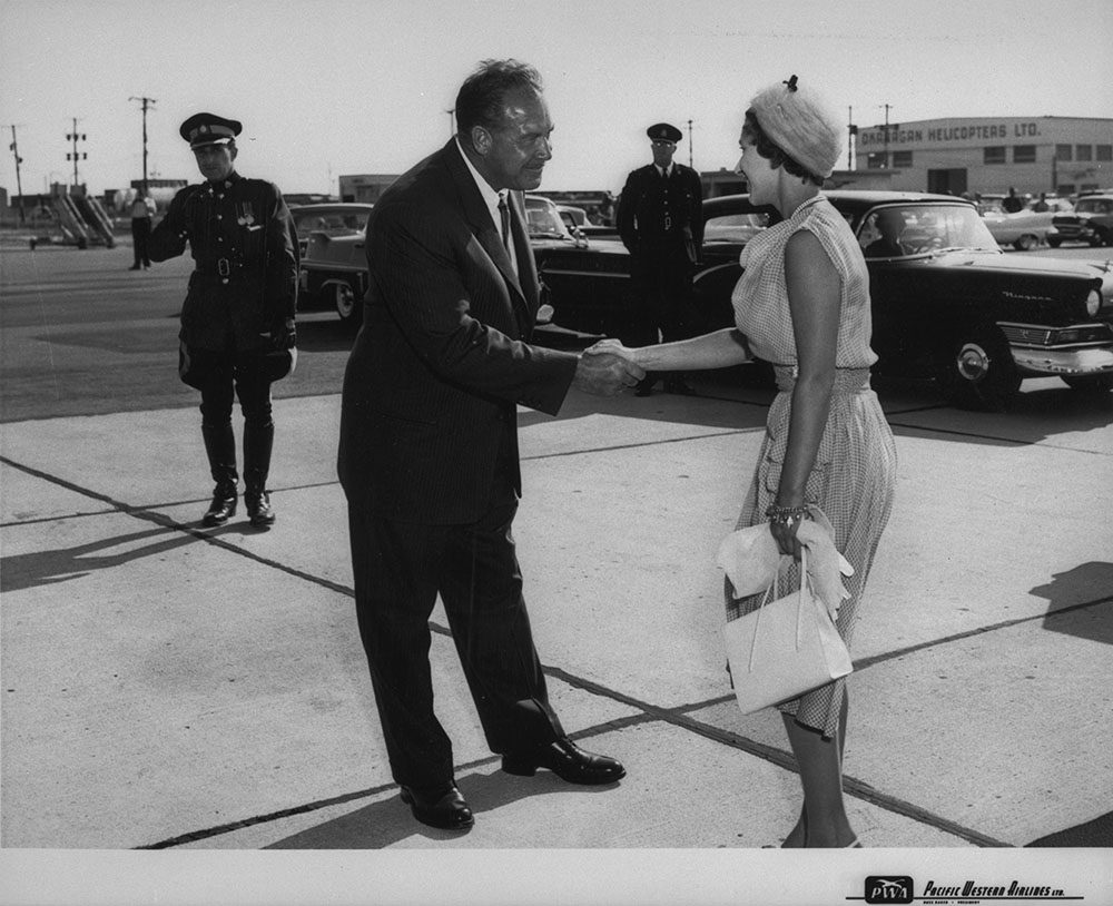 Russ Baker, President of Pacific Western Airlines greeting Princess Margaret in 1958 (Baker, Russell / Library and Archives Canada / PA-102414)
