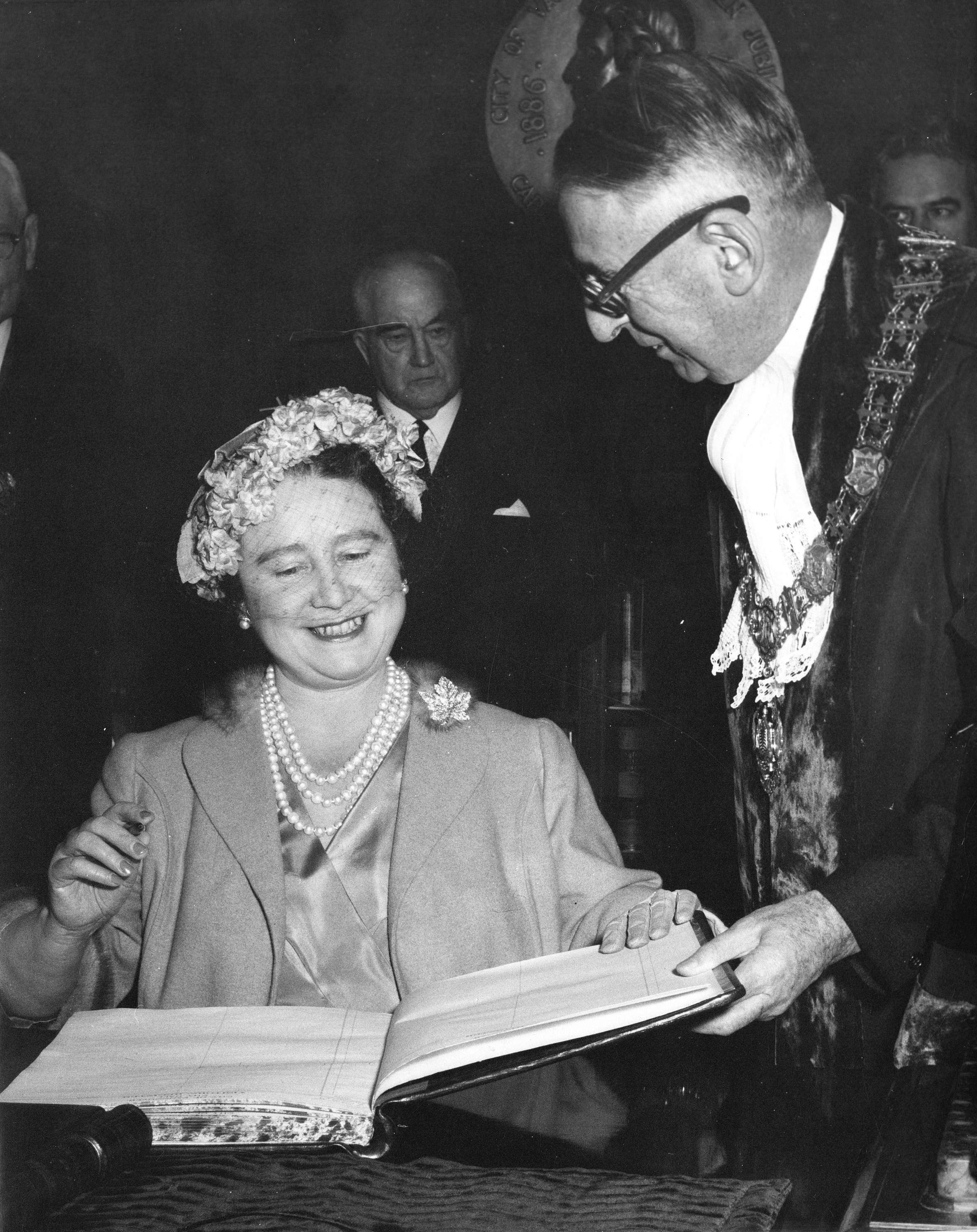 Queen Elizabeth the Queen Mother signs the guest book in the Mayor's office in Vancouver in 1958 (Public domain)