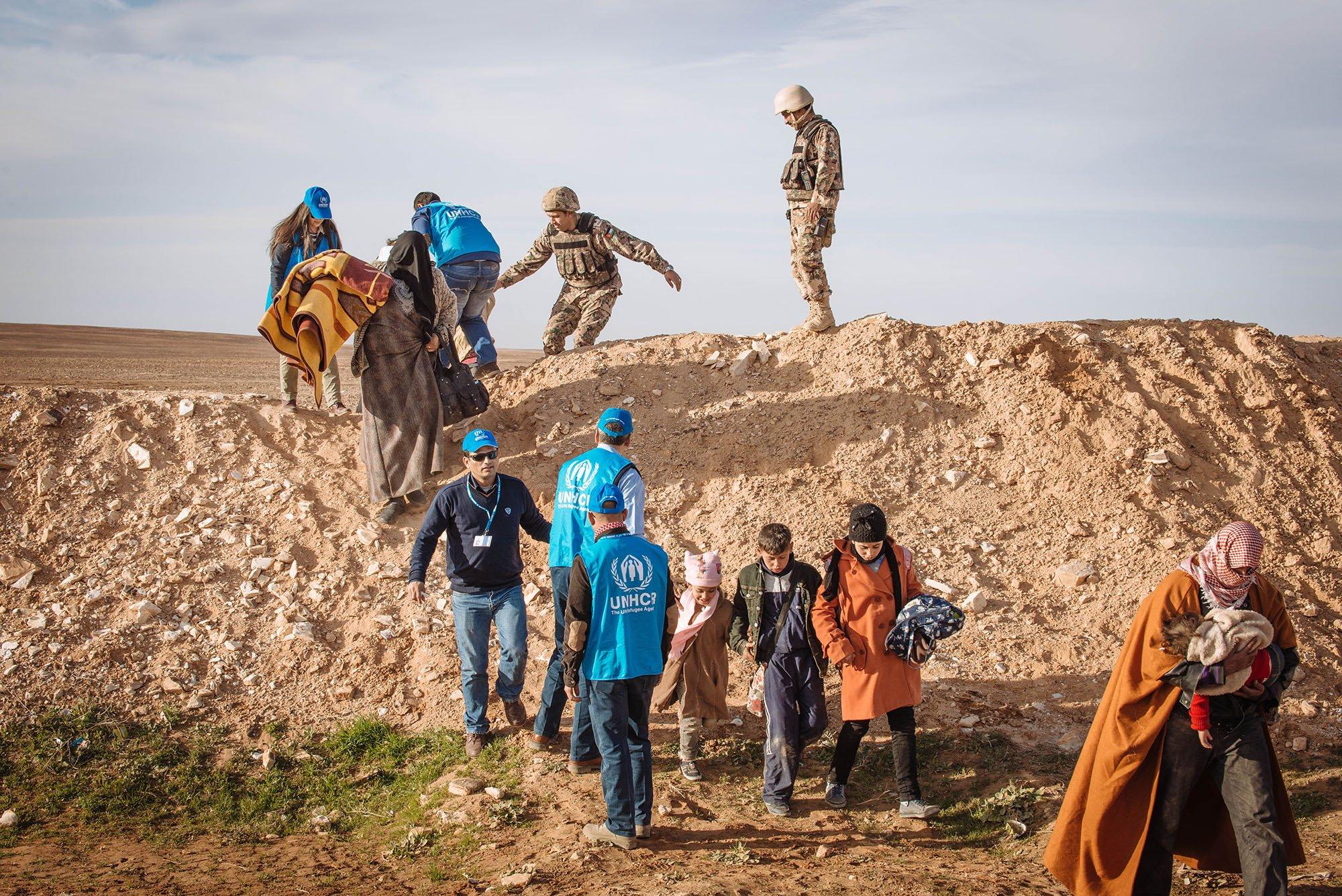 Syrian refugees walk the final metres across the desert toward the berm that marks the official Al-Ruwayshid Jordanian/Syrian border crossing. (UNHCR /J. Kohler)