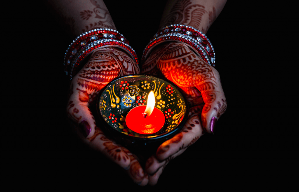 Diwali - Woman hands with henna holding lit candle (Pikoso.kz/Shutterstock)