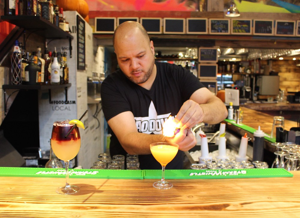 Using the flame to release the oils from the orange peel garnish (Lindsay William-Ross/Daily Hive)