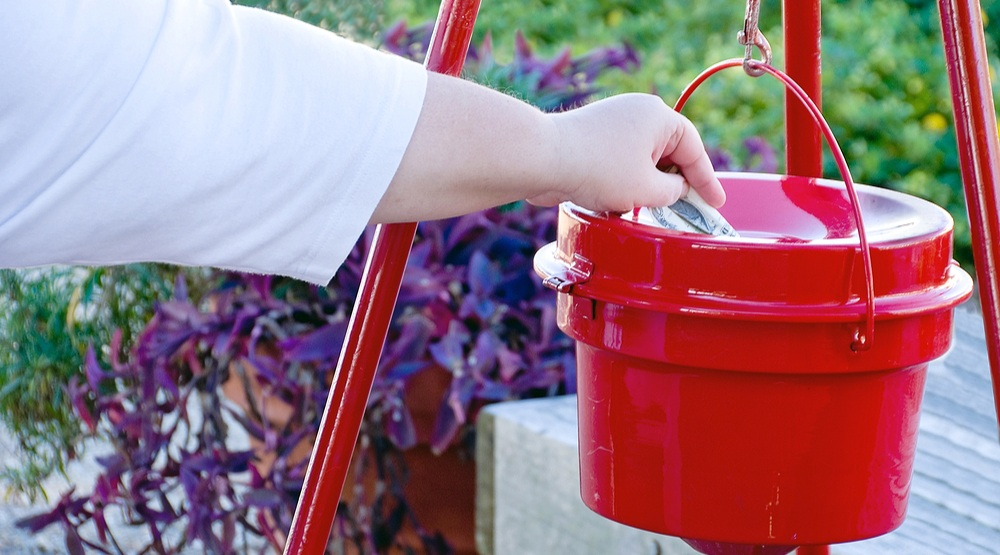 Person makes donation to The Salvation Army's Annual Christmas Kettle Campaign