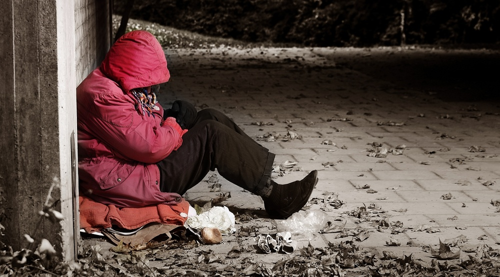 A homeless person huddling outside in cold weather shutterstock