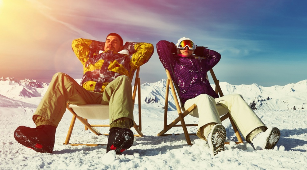 Man and woman in the snow and sunshine shutterstock