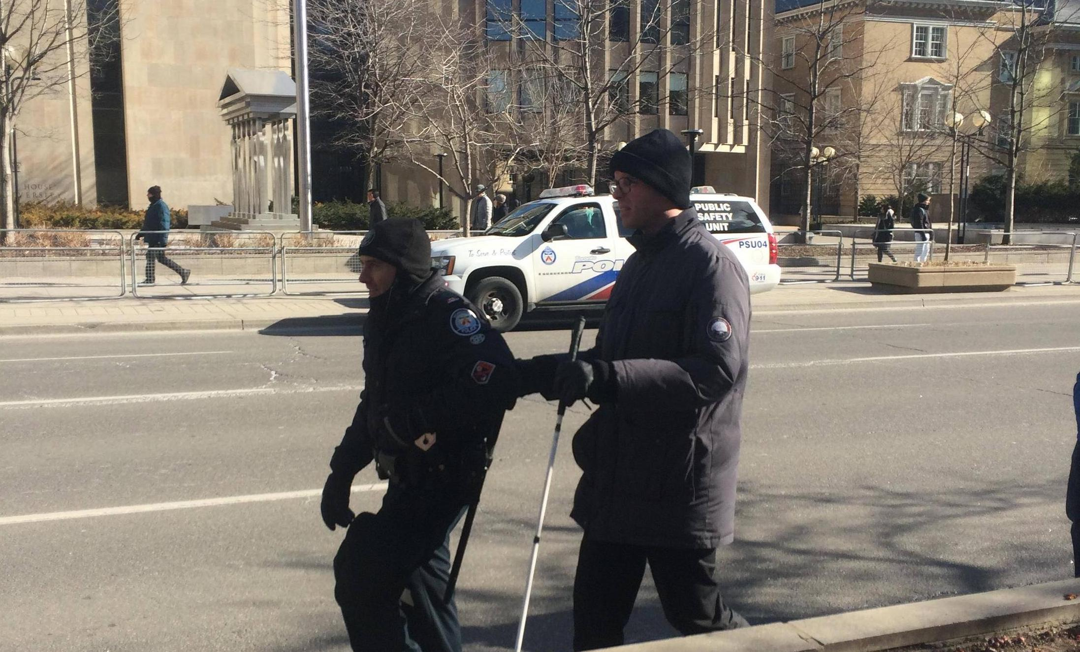 A Toronto police officer helped a man walk to the demonstration at the U.S Consulate