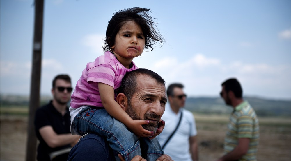 A Syrian man carries his daughter, as refugees abandon a makeshift camp in Greece (Giannis Papanikos/Shutterstock)