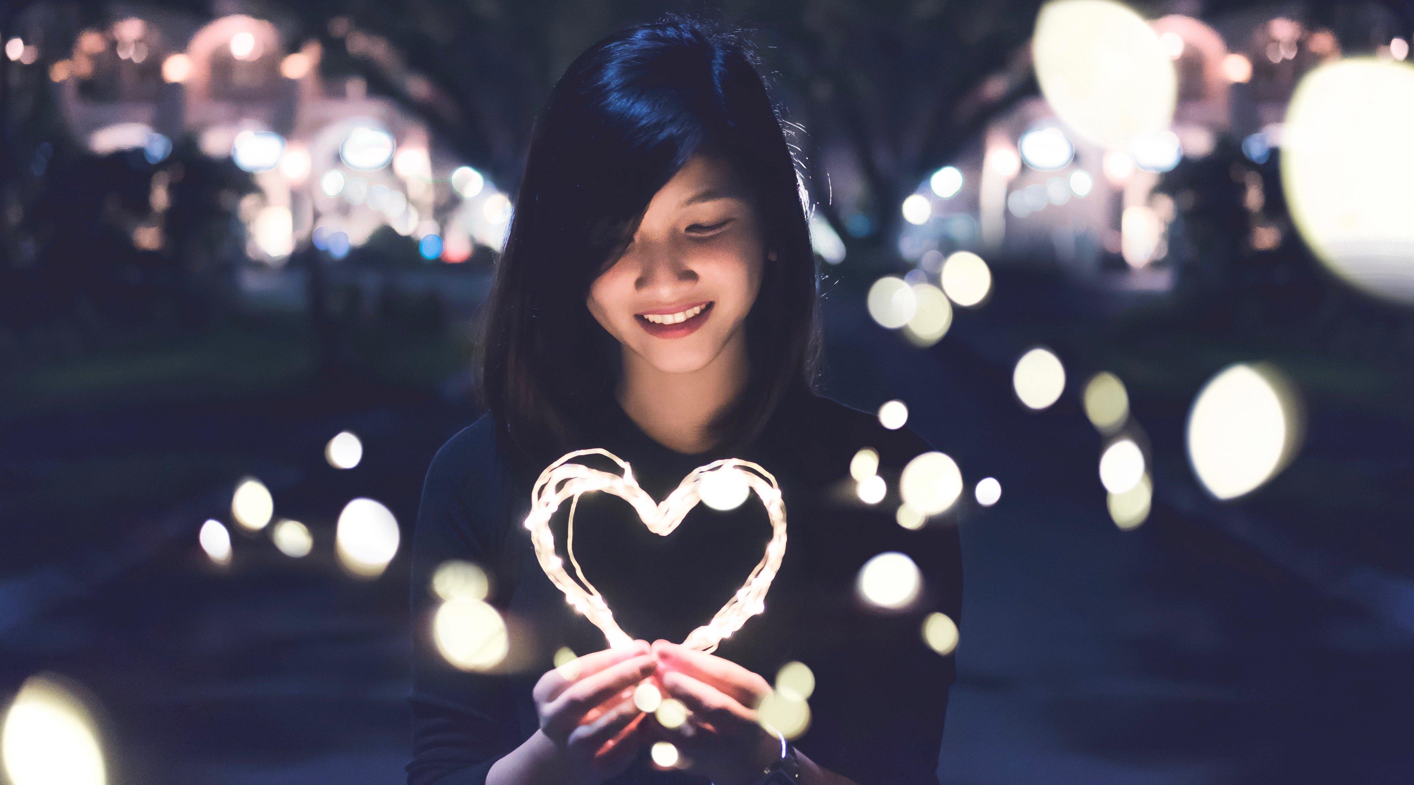Girl holding a light heart 1