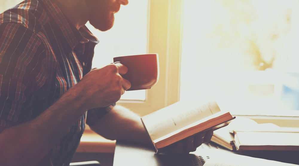 bearded man reading book with coffee