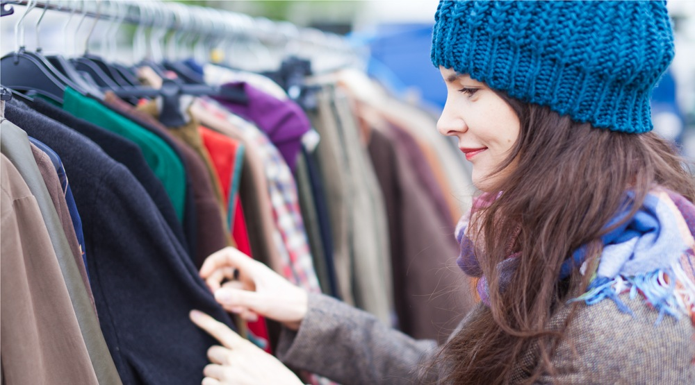 Woman in thrift store flea market vintage clothing shopping (Rishiken/Shutterstock)