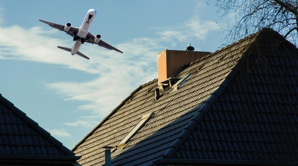Plane over houses shutterstock