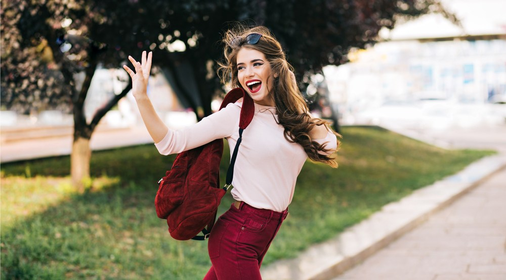 Woman walking looking happy waving (vfedorchenko/Shutterstock)