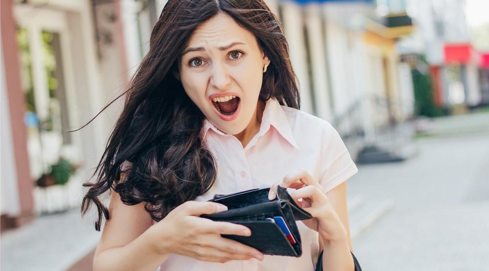 Shocked woman with no money (tanja-vashchuk/Shutterstock)