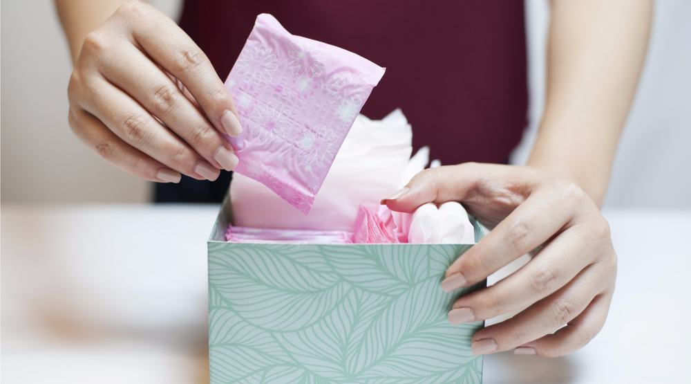 Woman with box of tampons and pads shutterstock