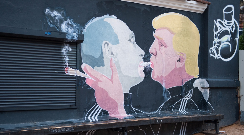 Graffiti showing Russian President Vladimir Putin and now US President Donald Trump kissing on the side of a barbecue restaurant in Lithuania in 2016 (JuliusKielaitis/Shutterstock)