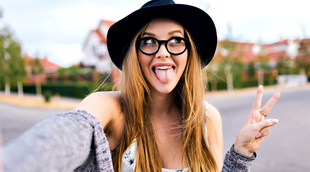Young blonde hipster woman, making selfie, showing tongue, funny face