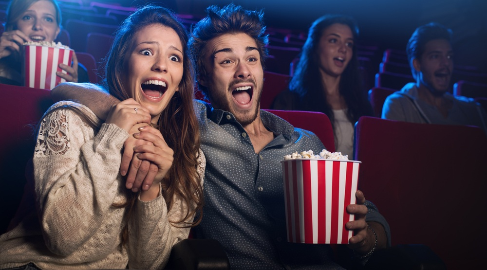 Young scared couple at the cinema watching an horror movie and screaming,