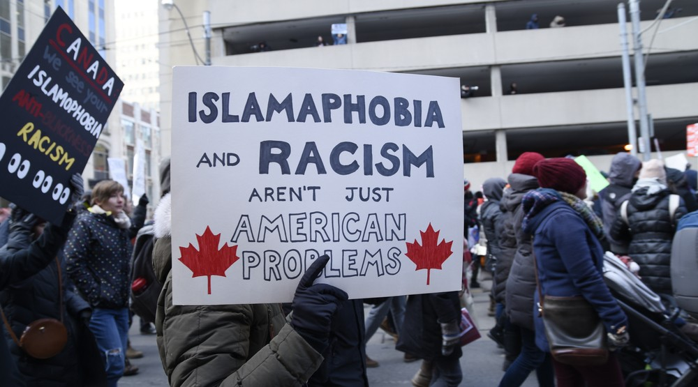 People with posters rejecting racism & Islamophobia during a protest in front of the US Consulate in Toronto in February, 2017 (arindambanerjee/Shutterstock)