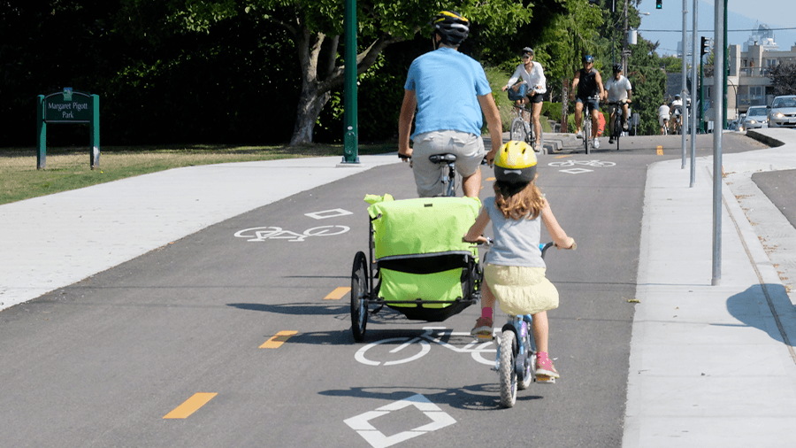 A parent and child cycling on a Vancouver bike path (HUB Cycling)