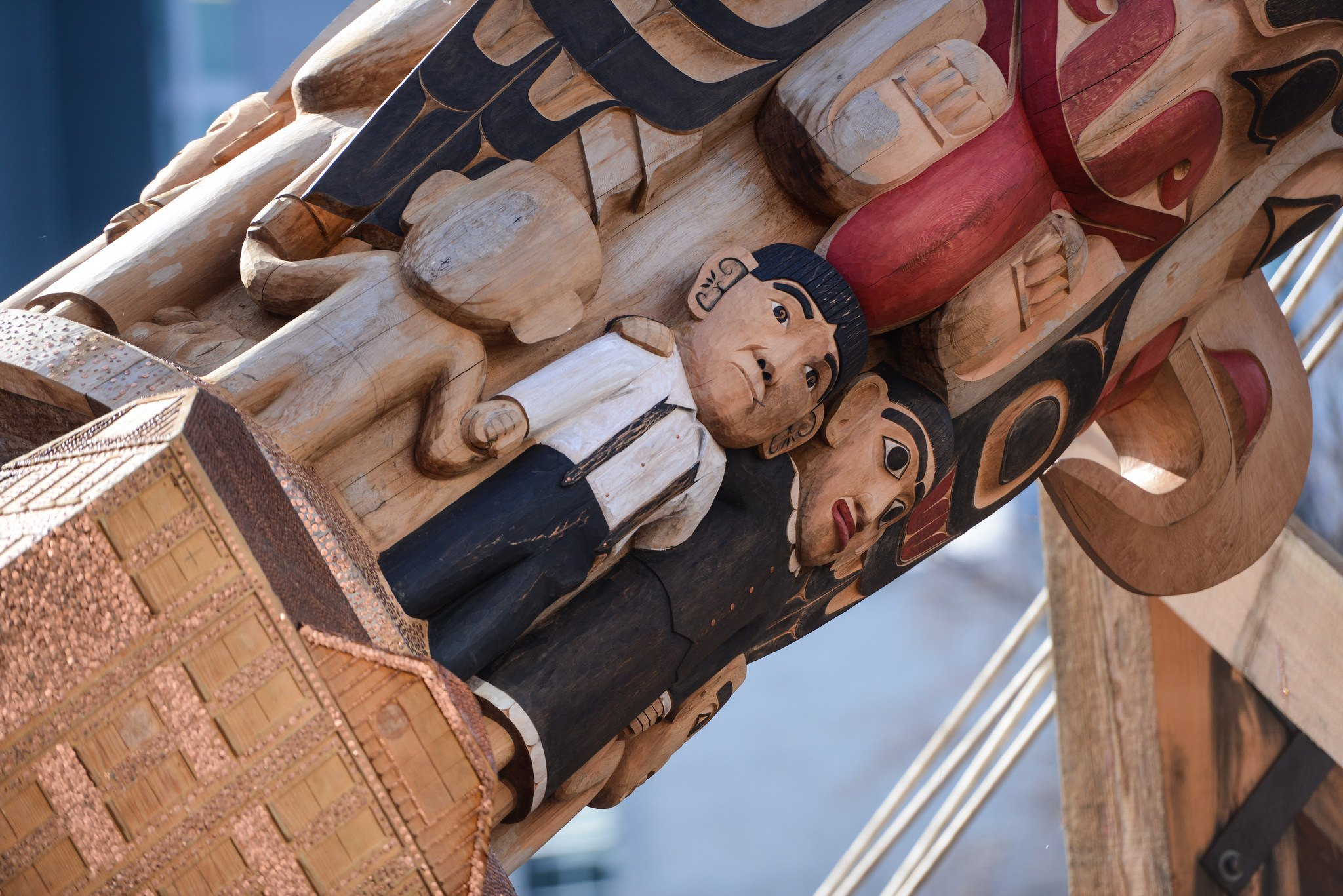 A depiction of indigenous people holding hands over a residential school on the new Reconciliation Pole at UBC (Paul Joseph/UBC)